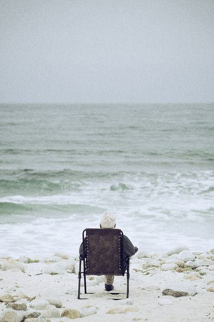 Elderly Person sitting looking at the sea